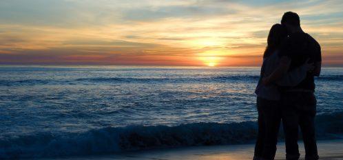 Couple enjoying a romantic sunset over the ocean